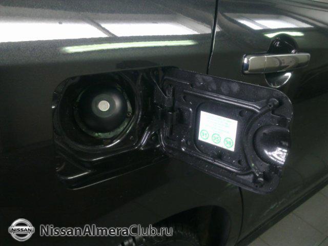 Nissan Almera АвтоВАЗ 2012: лючок бензобака. Новая Альмера всеядна - можно заливать хоть 92, хоть 95, хоть 98.